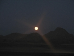 Moon setting behind hills